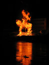 Bonfire great on the river bank with abandoned factory building in background Stock Images