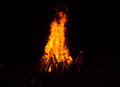 Bonfire a man throws wood into a glowing red orange and yellow in the dark night Royalty Free Stock Photography