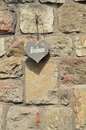 Bonheur stone wall with wooden heart shape with text which is french for happiness Stock Images