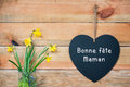 Bonne fete maman, French mothers day card, wood planks with daffodils and a blackboard in shape of a heart Royalty Free Stock Photo