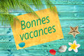 Bonnes vacances (meaning happy summer) written on a paper on colorful wood background with palm trees Royalty Free Stock Photo