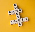 Bonuses bank and theft text inscribed on small white cubes in black uppercase letters arranged crossword style to suggest Royalty Free Stock Images