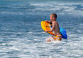 Boogie boarding in pacific ocean waves Stock Photos