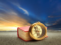 Book and compass at sunset sky with road
