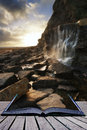Book concept beautiful landscape image waterfall flowing into ro rocks on beach at sunset Stock Photo