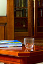 The book and a glass on the coffee table against background of bookcase Royalty Free Stock Photo