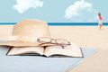 Book glasses and hat on the beach Royalty Free Stock Photo