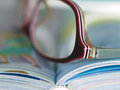 Book with glasses open color pages and eyeglasses in close Royalty Free Stock Image