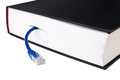 Book in hardcover with blue LAN patch cord. Royalty Free Stock Images