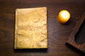 Book with leather covers an old illuminated by a candle on a wooden table Stock Image