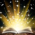 Book old open with magic light and falling stars on wood planks and dark abstract background Royalty Free Stock Images