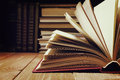 Book opened in library on wooden shelf. Education background with copy space for text. Toned photo Royalty Free Stock Photo