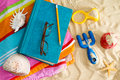 Book and reading glasses on a beach towel colorful sandy with plastic toys starfish seashells with parent Royalty Free Stock Image
