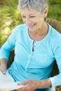 Book reading senior woman Royaltyfria Bilder