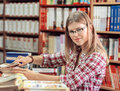Book shop owner female of or library putting books in order beautiful young blond salesperson in store Stock Image