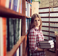 Book shop owner small business successful commerce woman in proper standing with books young ambitious female retailer among print Royalty Free Stock Photo