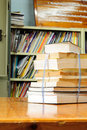 Book stack against book shelf in library Stock Image