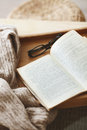 Book and sweater warm knitted a on a wooden tray Royalty Free Stock Photography