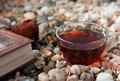 Book and transparent glass cup with tea standings Royalty Free Stock Photo