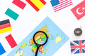 Booking trip with map, flags and tourist outfit on white office desk background top view