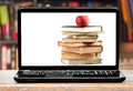 Books and apple on laptop screen Royalty Free Stock Photo