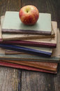 Books and apple old school stacked on a wooden table Stock Image
