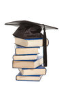 Books with black cap of bachelor isolated on white Royalty Free Stock Photo