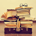 Books and eyeglasses in an old suitcase, with a retro effect Royalty Free Stock Photo