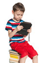 Books or a gadget concentrated young boy is sitting on the pile of and holding new Royalty Free Stock Image