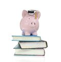 Books and piggy bank with graduation cap on a pile of Stock Image