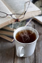 Books tea and glasses stack of with cup of selective focus Stock Images