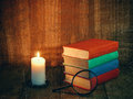 Books and a white candle on a wooden table. Reading by candlelight. Vintage composition. Royalty Free Stock Photo