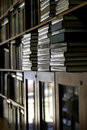 Bookshelves piled with books vertical Royalty Free Stock Images