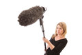 Boom operator woman holding a microphone against a white background selective focus on the furry microphone windshield Royalty Free Stock Photo