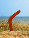 Boomerang on overgrown sandy beach. Stock Photo