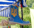 Boot with ukrainian symbols blue leather national emblem is hung in the shoemaker s pavilion at the ethnic festival Royalty Free Stock Photography