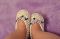 Bootee baby legs in knitting white slippers with purple roses on the arm Stock Images