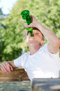 Boozer knocking back the alcohol gulping down contents of large green bottle of spirits as he sits outdoors in park low angle view Royalty Free Stock Photography