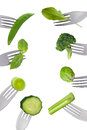 Border of fresh green vegetables isolated on forks Stock Images