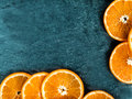 Border of fresh juicy orange slices arranged on two sides on a dark textured slate background with copyspace for your text Royalty Free Stock Image