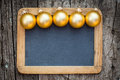 Border of gold christmas balls on vintage wooden blackboard blank Stock Photos