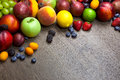 Border of mixed fruits with water drops on wooden texture Royalty Free Stock Photo