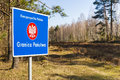 Border post with the emblem of the polish forest in background Stock Photo