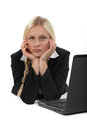 Bored blond office worker sat at her desk Stock Images