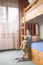 Bored boy with teddy bear leaning on bunk bed full length of young Royalty Free Stock Photo