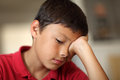 Bored boy young very student with hand covering his eye very shallow depth of field with copy space Stock Photo