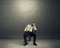 Bored businessman sitting in the room empty dark Royalty Free Stock Photos