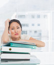Bored businesswoman with stack of folders at desk Royalty Free Stock Images