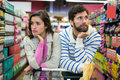 Bored couple with shopping trolley in organic section