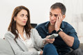 Bored couple watching tv frustrated looking at each other while television sitting on couch Royalty Free Stock Image